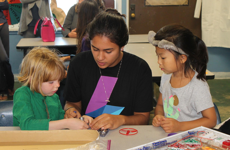 girl teaching two younger girls